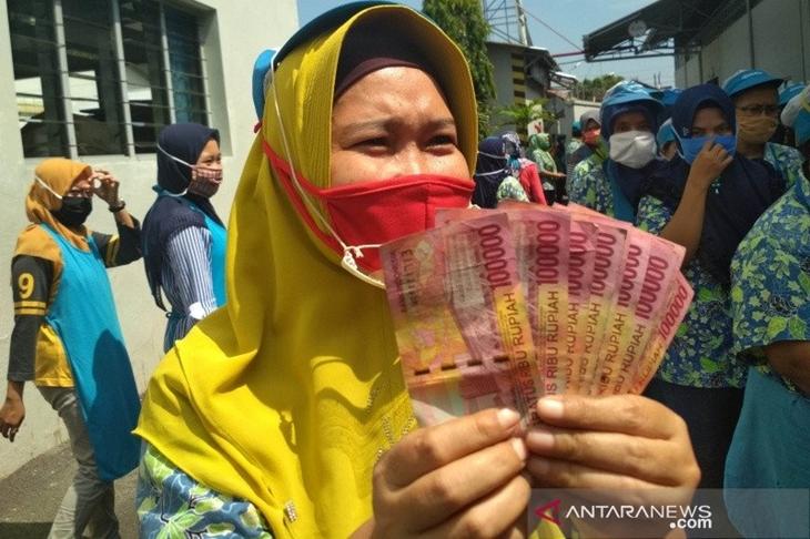 Ilustrasi - Seorang pekerja di Kabupaten Kudus, Jawa Tengah, menunjukkan uang tunjangan hari raya (THR). (ANTARA/Akhmad Nazaruddin Lathif)