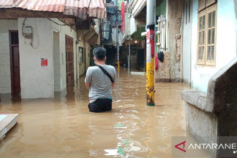 Warga Kebon Pala, Kampung Melayu, Jatinegara, Jakarta Timur, melintas di RT11 RW05 yang terendam banjir dengan ketinggian berkisar 50-70 sentimeter, Selasa (22/9). (ANTARA/Andi Firdaus)