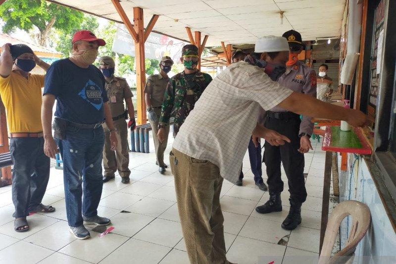 Persiapan menghadapi normal baru, agen tiket perusahaan otobus menerapkan protokol kesehatan COVID-19 dengan menyanitasi tangan di Terminal Kalideres, Jakarta, Sabtu (30/5/2020). (ANTARA/HO-Polres Metro Jakarta Barat)