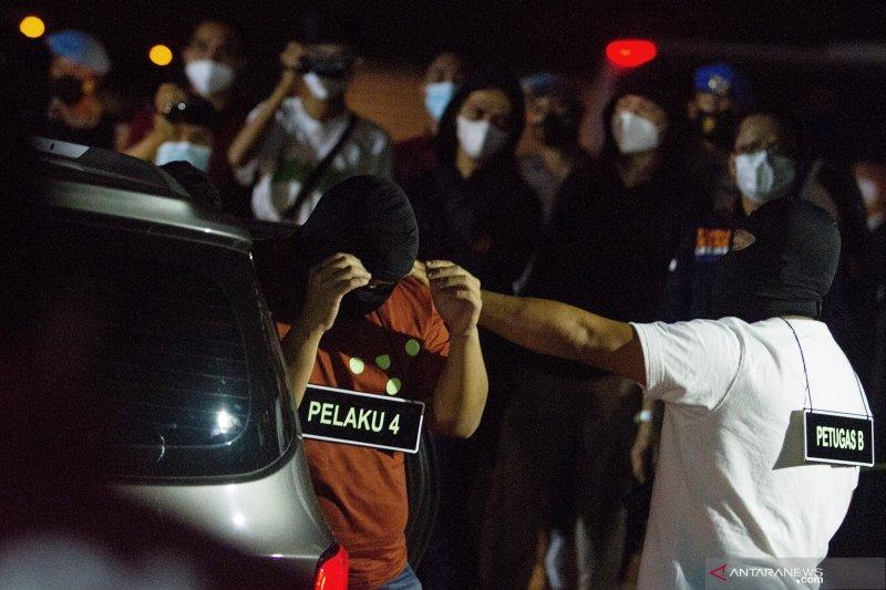 Sejumlah anggota tim penyidik Bareskrim Polri memperagakan adegan saat rekonstruksi kasus penembakan enam anggota laskar Front Pembela Islam (FPI) di Karawang, Jawa Barat, Senin (14-12-2020) dini hari. Rekonstruksi tersebut memperagakan 58 adegan kasus penembakan enam anggota laskar FPI di tol Jakarta-Cikampek KM 50 pada hari Senin (7-12-2020) di empat titik kejadian perkara. ANTARA FOTO/M. Ibnu Chazar/hp.